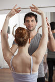 Trainer Teaching Ballet To Young Ballerina In Studio. Mid adult male trainer teaching ballet to female young dance in studio Royalty Free Stock Photos