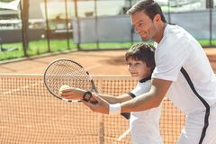 Trainer teaching boy to play tennis Royalty Free Stock Images