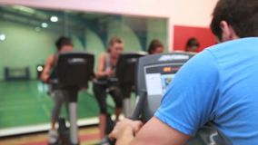 Trainer teaching spinning class. In gym stock video footage