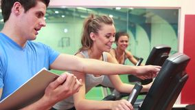 Trainer teaching two women on exercise bikes. In gym stock video footage