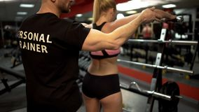 Trainer teaching woman to lift dumbbells gym, personal training program, sport. Trainer teaching women to lift dumbbells gym, personal training program, sport royalty free stock photography