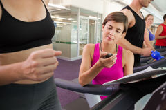 Trainer timing her client on the treadmill. At the gym stock photos