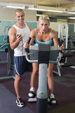Trainer timing his client on exercise bike at gym Royalty Free Stock Image