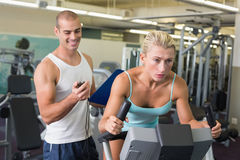 Trainer timing his client on exercise bike at gym Royalty Free Stock Photos