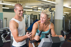 Trainer timing his client on exercise bike at gym. Smiling male trainer timing his client on exercise bike at the gym Stock Images