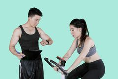 Trainer timing his client during exercise on studio. Picture of male trainer timing his client during uses exercise bike in the studio stock photos