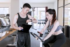 Trainer timing his client during use an exercise bike. Picture of male trainer timing his client during use an exercise bike in the fitness center royalty free stock photos