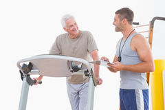 Trainer timing senior man. Trainer timing senior men in fitness studio stock images