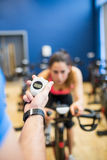 Trainer timing woman on exercise bike. At the gym Royalty Free Stock Image