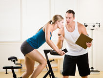 Trainer timing woman on stationary bicycle. Trainer timing a woman on a stationary bicycle royalty free stock photos
