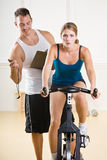 Trainer timing woman on stationary bicycle. Personal trainer timing a woman on a stationary bicycle royalty free stock photo