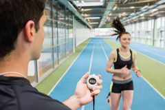Trainer timing woman on the track. Trainer timing women on the track at the gym stock images