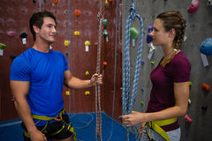 Trainer training female athlete in climbing wall at club Royalty Free Stock Photography