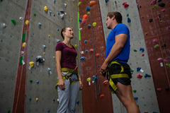 Trainer training female athlete in climbing wall at gym Stock Photo