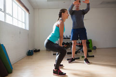 Trainer training woman in lifting kettlebells at fitness studio. Male trainer training women in lifting kettlebells at fitness studio Stock Photography