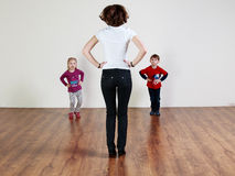 Trainer and two children are doing exercises royalty free stock images