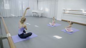 The trainer and two girls sit tailor-fashion on the mats in the ballet class. The blonde female ballerina teaches kids how to bend sideways beautifully with stock video