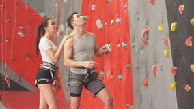Trainer typing harness of woman on climbing wall in gym stock footage