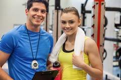 Trainer und Frau, die Trainingsplan besprechen Lizenzfreie Stockfotos