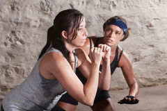 Trainer Watching Athlete During Boot Camp Training. Trainer watching over young athlete exercising indoors Royalty Free Stock Photo