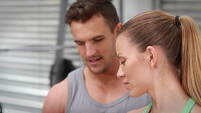 Trainer watching client lift dumbbells at crossfit gym. In high quality 4k format stock footage