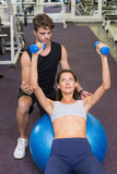 Trainer watching client lying on exercise ball with dumbbells Royalty Free Stock Photography