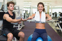 Trainer watching client sitting on exercise ball. At the gym Royalty Free Stock Photography