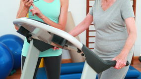 Trainer watching elderly client using treadmill stock footage