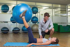 Trainer watching his client lift exercise ball with legs Royalty Free Stock Photos