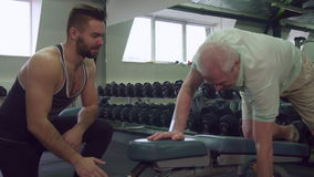 Trainer watching how senior client does exercises stock video