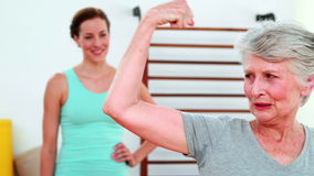 Trainer watching proud elderly client flexing her bicep. At the rehabilitation center stock video