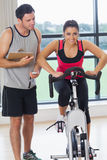 Trainer watching woman work out at spinning class Royalty Free Stock Image