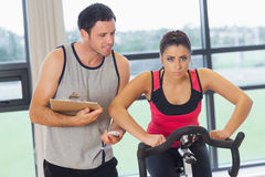 Trainer watching woman work out at spinning class Stock Images