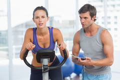 Trainer watching woman work out at spinning class Royalty Free Stock Photo