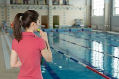 Trainer woman blowing whistle and standing with his back near poolside. Copyspace Stock Images