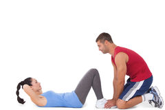 Trainer with woman doing sit ups Stock Photos