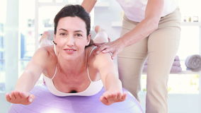 Trainer with woman on exercise ball. In fitness studio stock footage