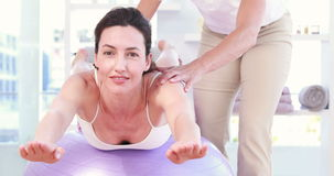 Trainer with woman on exercise ball. In fitness studio stock video footage