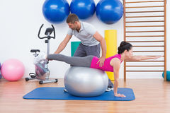 Trainer with woman on exercise ball Royalty Free Stock Photo