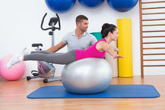 Trainer with woman on exercise ball Stock Photography