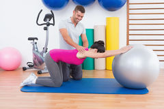 Trainer with woman on exercise ball Royalty Free Stock Image