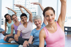 Trainer with women in row stretching hands at yoga class Stock Image