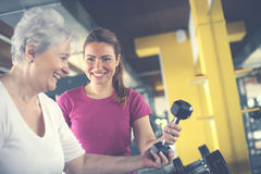 Trainer working exercise with senior woman in the gym. Personal trainer working exercise with senior women in the gym. Woman picking weight. Workout in gym royalty free stock photo