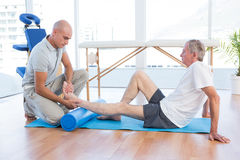 Trainer working with man on exercise mat Stock Photo
