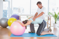 Trainer working with woman on exercise ball Royalty Free Stock Images