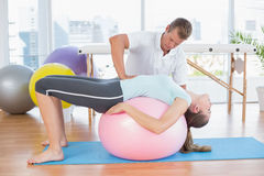 Trainer working with woman on exercise ball Royalty Free Stock Photography