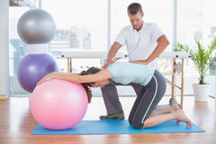 Trainer working with woman on exercise ball Stock Photography