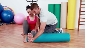 Trainer working with woman on exercise mat stock footage