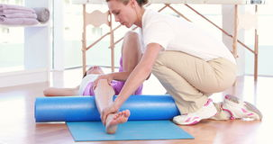 Trainer working with woman on exercise mat stock video footage