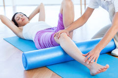 Trainer working with woman on exercise mat Royalty Free Stock Photo